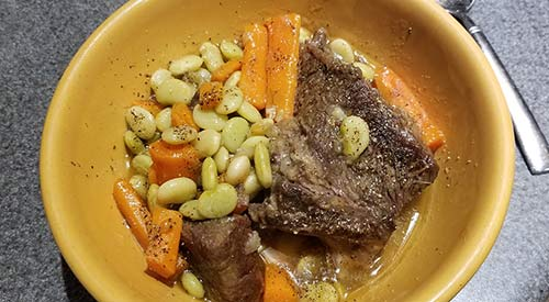 A serving bowl of short ribs and vegetables